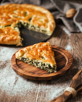 Spinach filling pie on the wooden rustic table