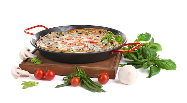 Spinach frittata in pan and vegetables, isolated on white
