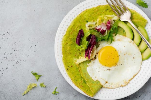 灰色のコンクリートの背景にセラミック プレートに目玉焼き、アボカド、サラダのミックスの葉とほうれん草の緑のクレープ (パンケーキ)。 〇ヘルシーな朝食のコンセプト。選択と集中。上面図。コプトスペース。