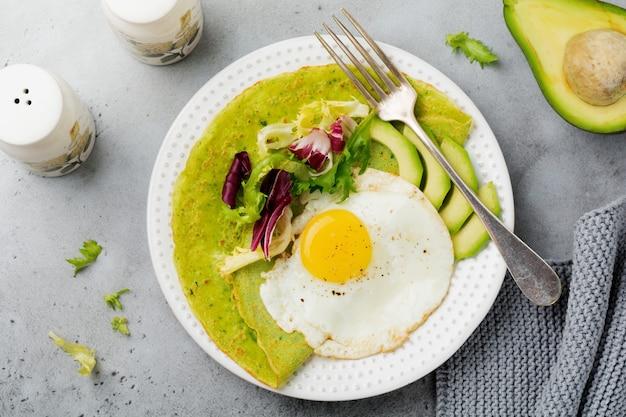 灰色のコンクリート表面のセラミックプレートに目玉焼き、アボカド、サラダのミックスの葉を添えたほうれん草のグリーンクレープ(パンケーキ)。上面図。コプトスペース。
