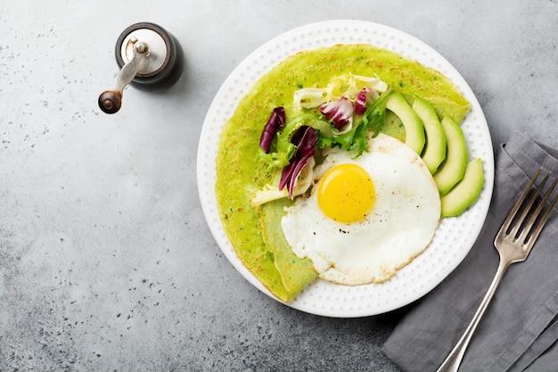 灰色のコンクリート テーブルのセラミック プレートに目玉焼き、アボカド、サラダのミックスの葉とほうれん草の緑のクレープ (パンケーキ)。健康的な朝食のコンセプト。選択と集中。上面図。コプトスペース。