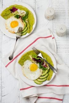 ほうれん草グリーン クレープ (パンケーキ) 目玉焼き、アボカド、白い木製の背景にセラミック プレートにサラダのミックスの葉。 〇ヘルシーな朝食のコンセプト。選択と集中。上面図。コプトスペース。