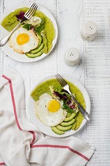 白い木の表面にセラミック プレートに目玉焼き、アボカド、サラダのミックスの葉とほうれん草の緑のクレープ (パンケーキ)。健康的な朝食のコンセプト。選択と集中。上面図。コプトスペース。
