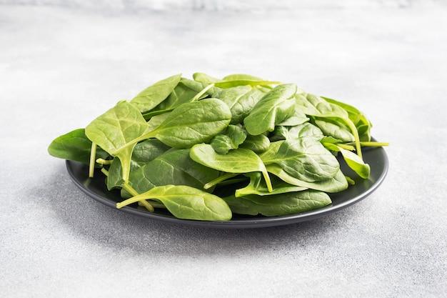 ほうれん草の緑の新鮮な葉を黒いプレートに。灰色のテーブル、コピースペース。