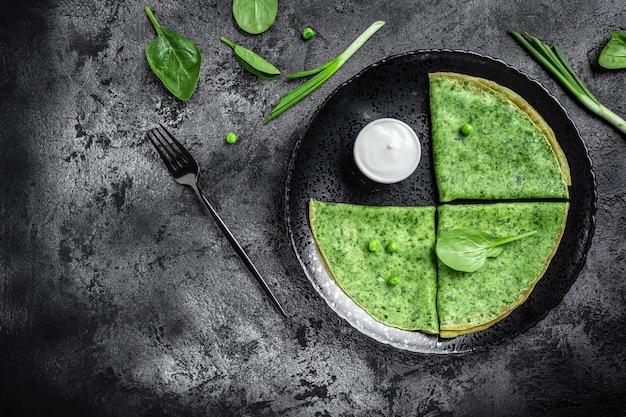 Блинчики со шпинатом и зелеными блинчиками со сметаной. вкусный здоровый завтрак. баннер, место рецепта меню для текста, вид сверху.