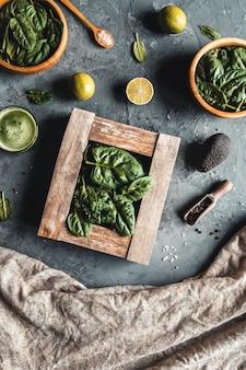 나무 상자에 시금치. 건강 식품 개념. 어두운 회색 배경에 나무 접시입니다.