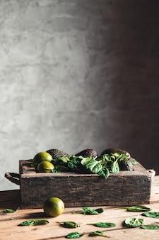 ライムとアボカドの入った古い箱に入ったほうれん草。健康食品、ビーガン、エコ、ウェルネス、ビンテージスタイル