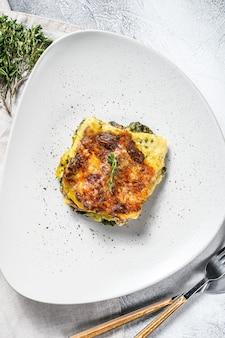 ほうれん草のラサニャオンプレート、ベジタリアン料理。白色の背景。上面図。