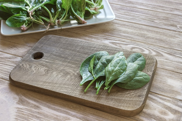 Spinach leave on cutting boards, plate of spinach