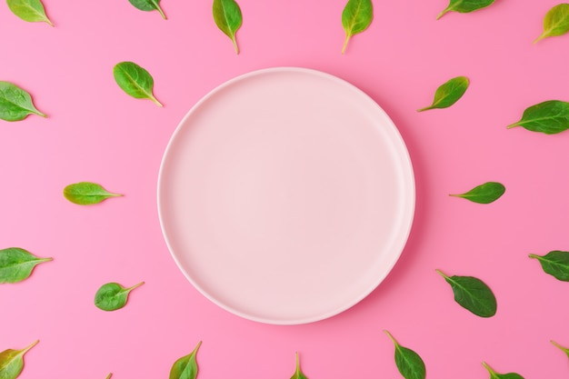 Spinach leaves around empty plate on pink background
