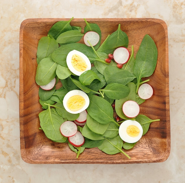 Spinach leaves, eggs, radishes and pomegranate seeds