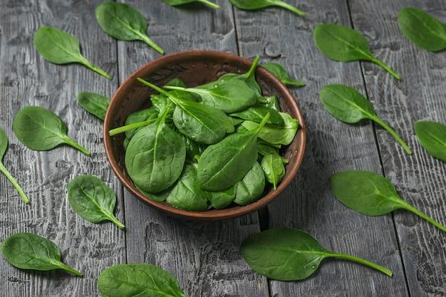 시금치는 점토 그릇과 검은 나무 테이블에 나뭇잎. 건강을 위한 음식. 채식주의 자 음식. 정상에서 본 모습.