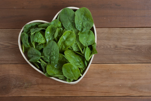 Spinach leaves isolated, heart shaped wooden plate.