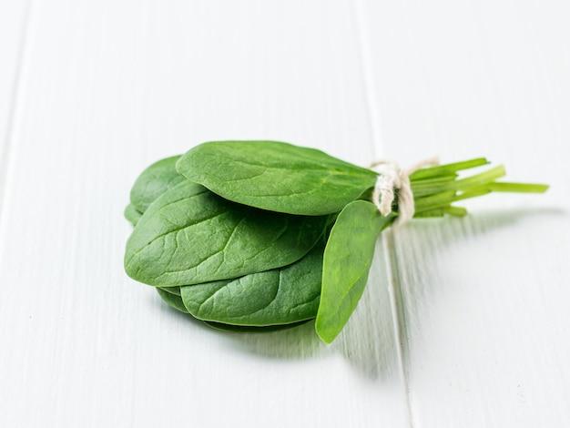 흰색 나무 테이블에 밧줄로 묶인 시금치 잎. 건강을 위한 음식. 채식주의 자 음식. 정상에서 본 모습.