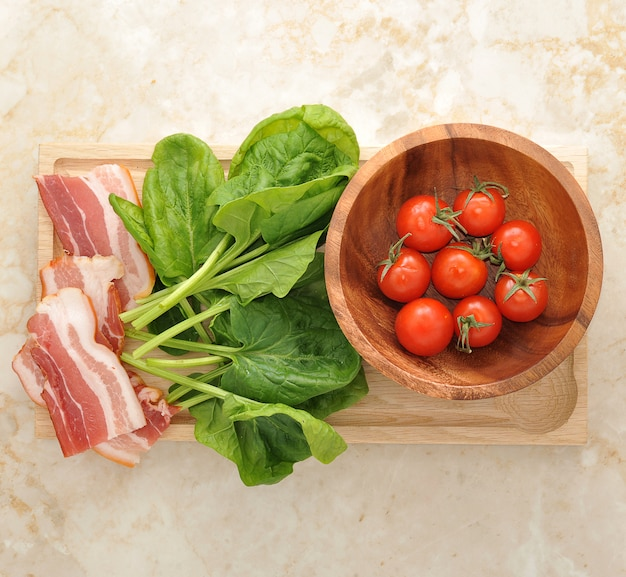 Spinach leaves and tomatoes and bacon