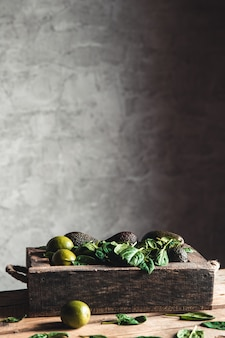 Spinach in an old box with lime and avocado. healthy food, vegan, eco, wellness, vintage style