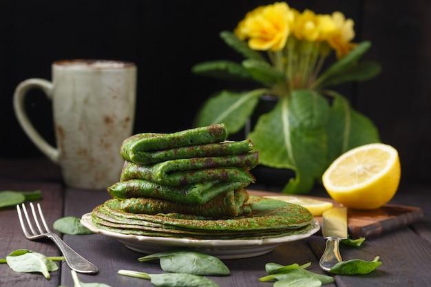 木製のテーブルと黄色のサクラソウのほうれん草のパンケーキ。