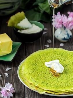 ほうれん草のパンケーキとサワークリーム、メープルシロップをグリーンのパンケーキに注ぐ