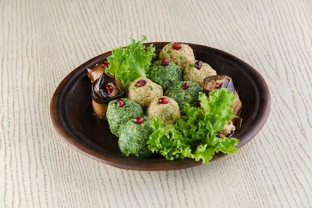 ほうれん草のファリ、ナスのロール、レタスとザクロを添えて。白い木製のテーブルの上の粘土板にグルジアの前菜。