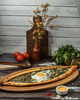 Spinach pide with egg on wood serving board