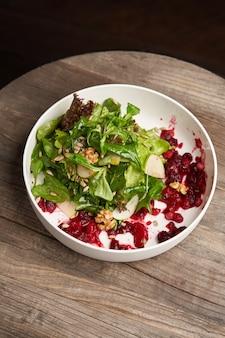 Салат из шпината в белой миске. салат здорового питания с листьями шпината, грецкими орехами, фруктами и овощами