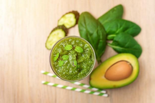 시금치 스무디. 가벼운 나무 테이블에 재료로 건강 한 녹색 주스. 평면도