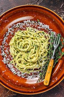 ほうれん草のスパゲッティパスタとペストソースとパルメザンチーズ。暗い背景。上面図。