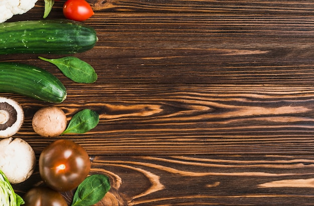 Spinach and vegetables on wooden tabletop