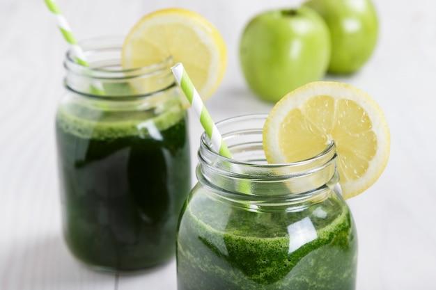 ほうれん草とレモンとリンゴジュースの白い木製のテーブルにストローとソフトドリンクジャー