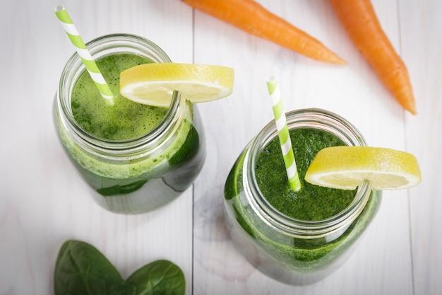ほうれん草とレモンとにんじんジュース白い木製のテーブルにストローとソフトドリンクジャー