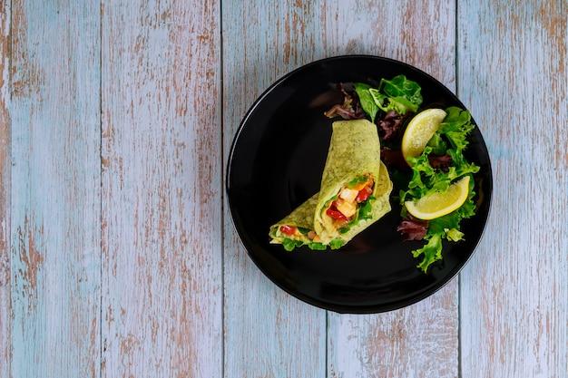 Обертывание из шпината с мясом и овощами на черной тарелке с зеленым салатом