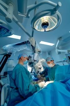 Спинальная хирургия. группа хирургов в операционной с хирургическим оборудованием. доктор смотрит на экран. современное медицинское образование