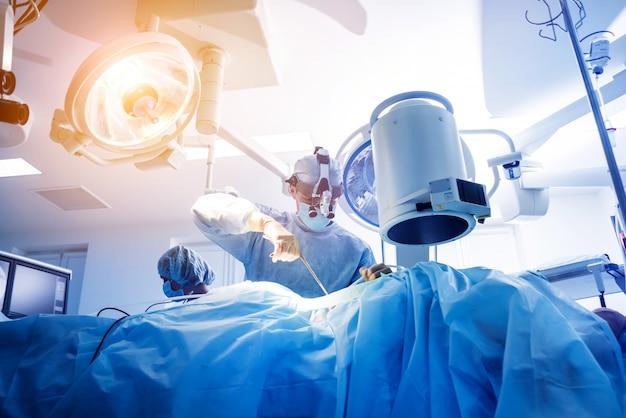 Спинальная хирургия. группа хирургов в операционной с хирургическим оборудованием.