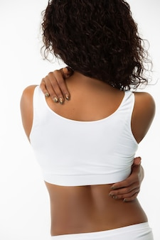 Spine and back. slim tanned woman's back on white studio background. african-american model with well-kept shape and skin. beauty, self-care, weight loss, fitness, slimming concept. healthcare.