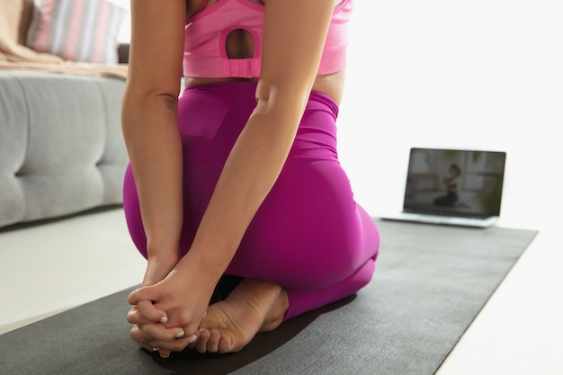 Позвоночник. закройте вверх красивой молодой женщины, работающей в помещении, делая упражнения йоги на сером циновке, деталях. практика неузнаваемой кавказской модели. концепция здорового образа жизни, внимательности, баланса.