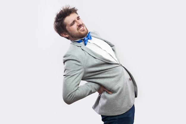 Боль в позвоночнике или почках. профиль вид сбоку портрет молодого бородатого бизнесмена в повседневном сером костюме и синем галстуке-бабочке, стоящего и держащего его болезненную спину. студийный снимок, изолированные на светло-сером фоне