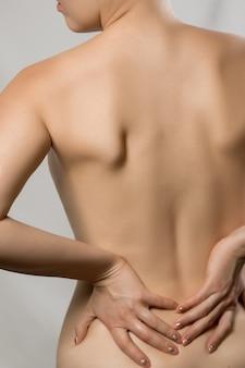 脊椎骨粗鬆症腰痛脊柱側弯症女性の背中の脊髄の問題美しい裸の女性が背中の痛みに触れている