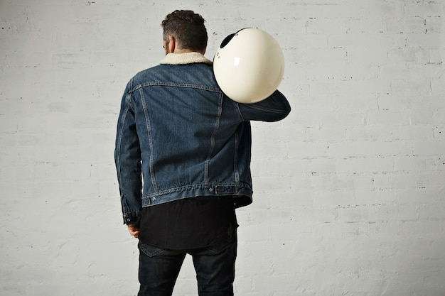 Spine view of biker wears shearling denim jacket and black blank henley shirt, holds vintage beige motorcycle helmet, isolated in center of white brick wall