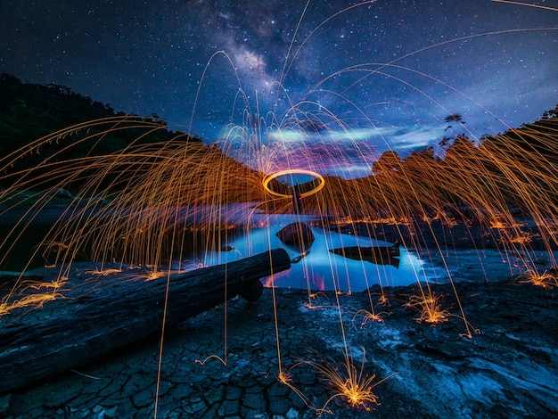 Spinning fire show among the stars in the sky