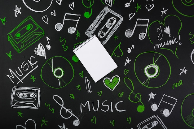 Спиральный пустой блокнот над доской с нарисованными музыкальными нотами; кассетные ленты; компакт-диски