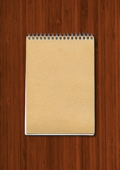 Spiral closed notebook , brown paper cover, isolated on dark wood surface