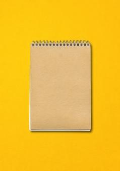 나선형 닫힌 노트북, 갈색 종이 커버, 노란색 배경에 고립