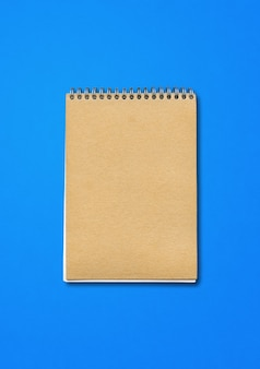 Spiral closed notebook mockup, brown paper cover, isolated on blue background