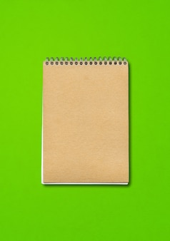 Спиральный закрытый макет ноутбука, обложка коричневой бумаги, изолированные на зеленом фоне