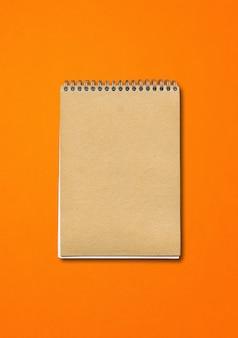Спиральный закрытый макет ноутбука, обложка коричневой бумаги, изолированные на оранжевом