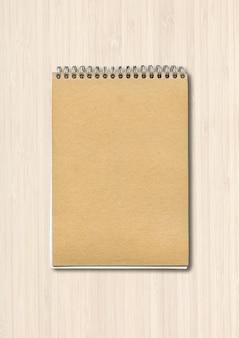 白い木で隔離のスパイラル閉じたノートブックモックアップ茶色の紙カバー