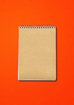Spiral closed notebook mockup, brown paper cover, isolated on red background