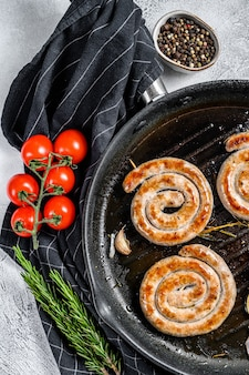 Spiral delicious grilled sausages with vegetables in pan. gray background.