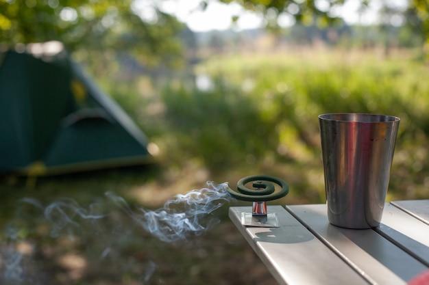 모기의 나선은 캠핑 텐트의 배경에 대해 금속 유리 옆 테이블에 서있는 동안 담배를 피우고 있습니다