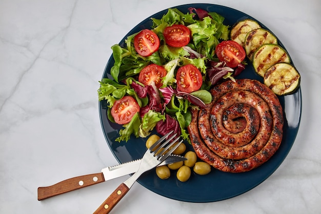 大理石のテーブルにカトラリーを添えた青いプレートにトマトとハーブ、ズッキーニとオリーブを添えたスパイラルグリルソーセージ